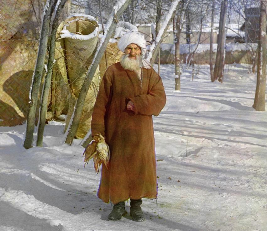Stariji čovjek nosi ptice u sniježno doba godine.