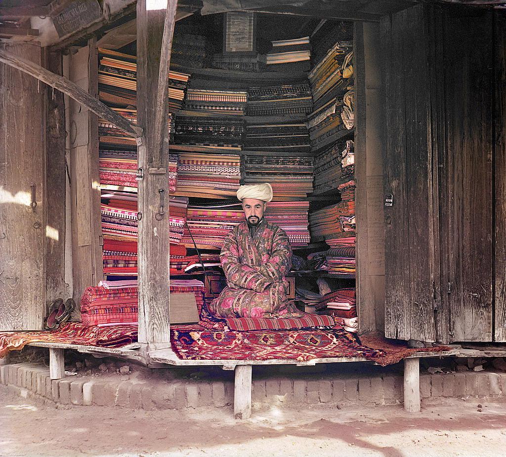 Trgovac tkaninom u Semerkandu sjedi za svojom tezgom.
