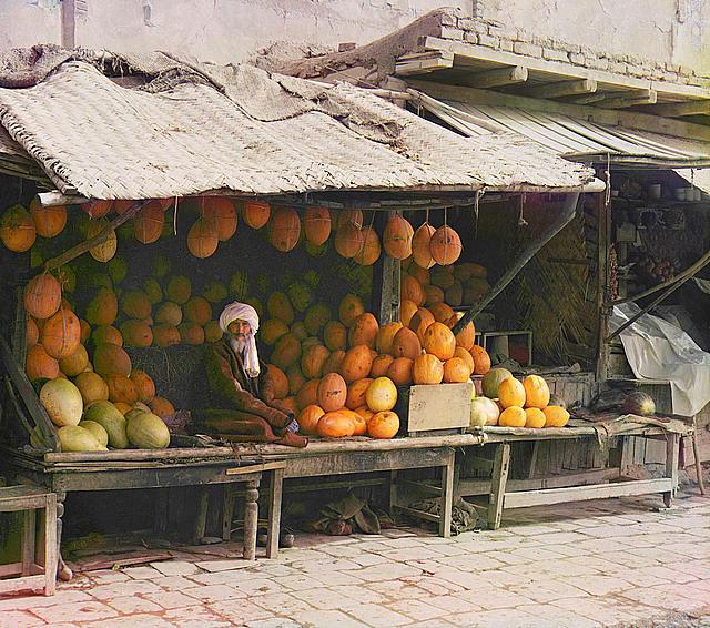 Trgovac voćem sjedi za svojom tezgom.