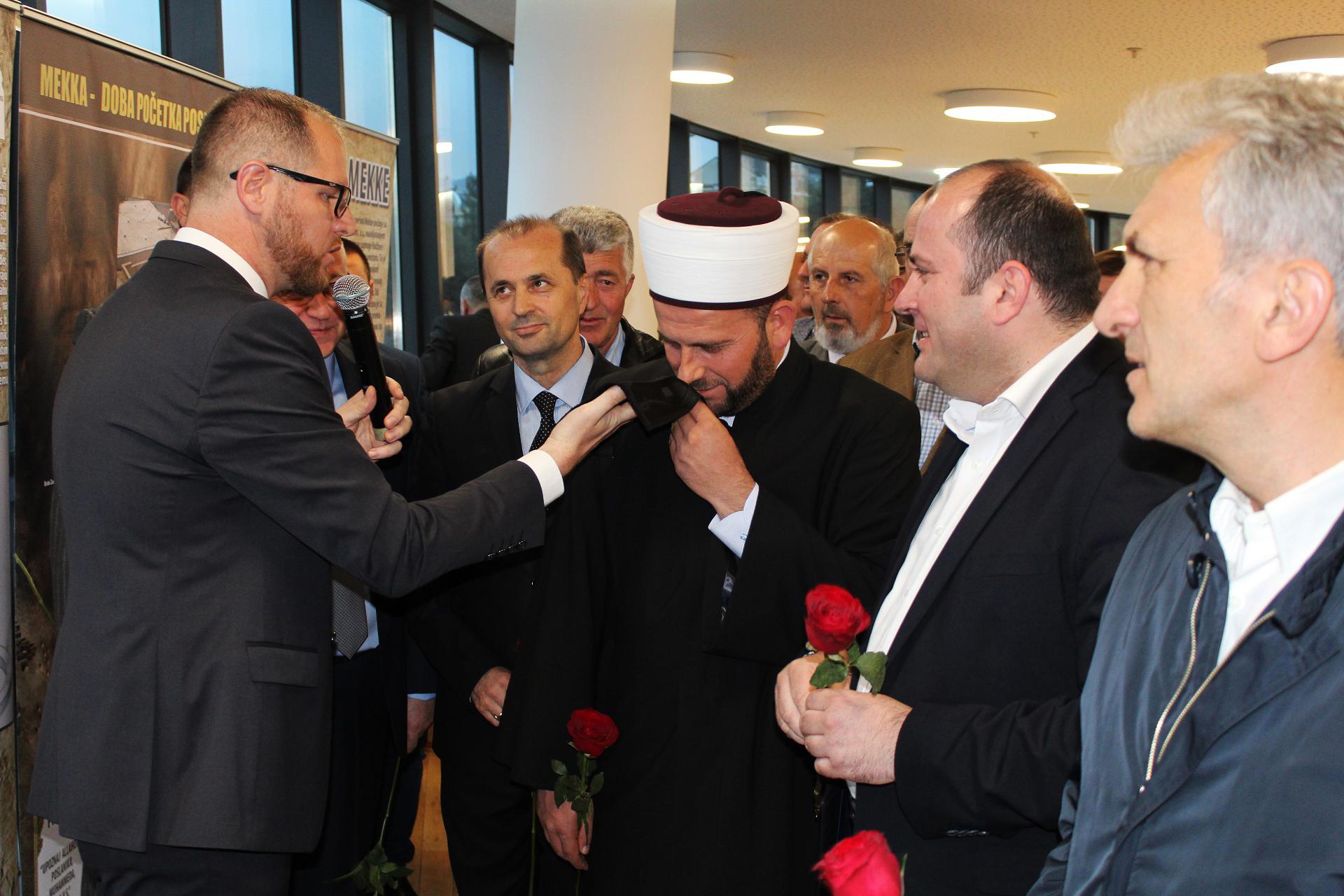 Autor izložbe doc. dr. Esmir Halilović pokazuje Kisvu, dio ogrtača Kabe Reisul-ulemi i ministru Pavlu Goranoviću.
